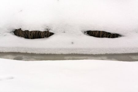 smiley face car: River in frost and snow resembling ghost face. Abstract seasonal background.