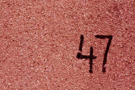 붉은 석고 벽에 번호 47. 추상적 인 배경입니다.