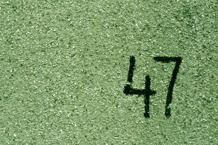 number fourty seven on green plaster wall. abstract background.