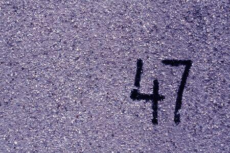파란 석고 벽에 번호 47. 추상적 인 배경입니다.
