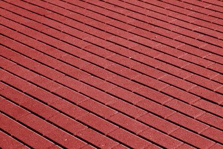 赤い色調の石畳の舗装面パターン。背景とテクスチャ。 写真素材
