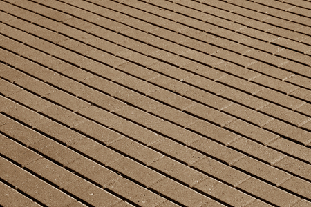 茶色の色調の石畳の舗装面パターン。背景とテクスチャ。