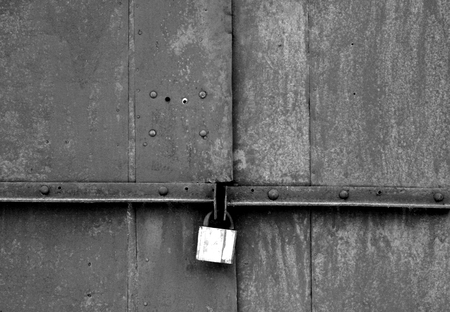 Old padlock on metal gate in black and white. Abstract background and texture.