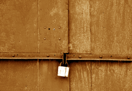 Old padlock on metal gate in brown tone. Abstract background and texture.