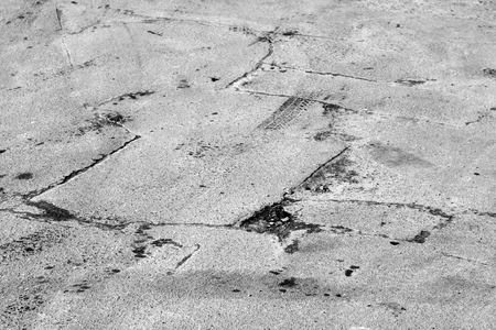 Damaged asphalt road in black and white. Abstract background and texture.