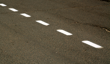 White paint markings on asphalt road. Abstract background and texture for design.
