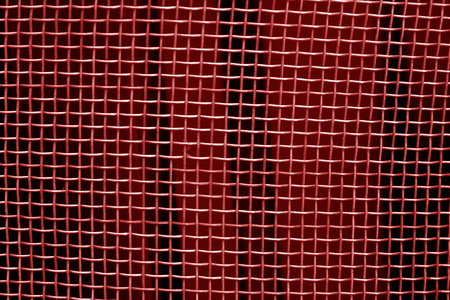 Metal mesh grid pattern in red tone. Abstract background and texture.