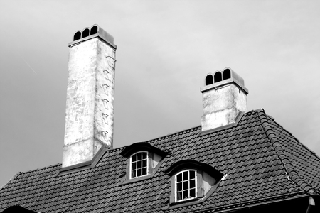 Old historic building roof with chimneys and windows in black and white. Urban background and texture.
