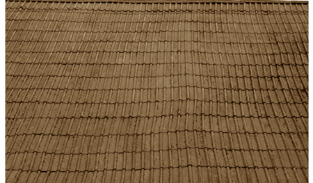 Old uneven shingles roof with blur effect in brown tone. Abstract background and texture for design. Stock Photo