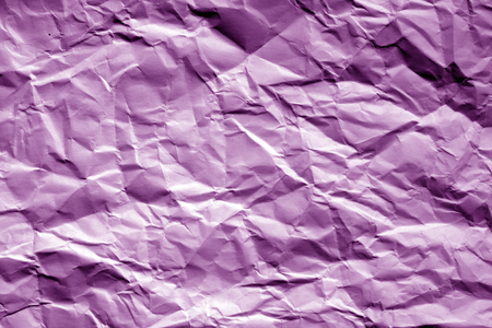 Crumpled sheet of paper in purple tone. Abstract background and texture for design.