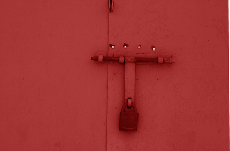 Old padlock on metal gate in red color. Abstract background and texture. Reklamní fotografie