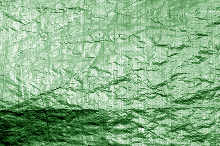 Crumpled transparent plastic  surface in green color. Abstract background and texture for design.