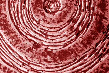 Part of old ceramic plate close-up in red tone. Abstract background and texture for design.