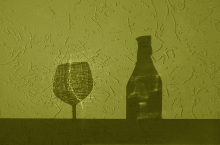 Wine bottle and glass shadow in yellow tone. Abstract backround and view. Stock Photo