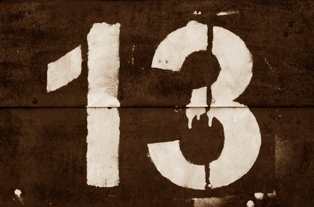 Number 13 in stencil on metal wall in brown tone. Abstract background and texture for design.