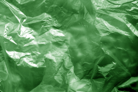 Crumpled transparent plastic surface in green tone. Abstract background and texture for design.