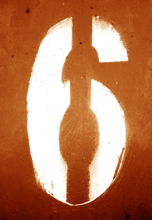 Number 6 in stencil on grungy metal wall in orange tone. Abstract background and texture for design.