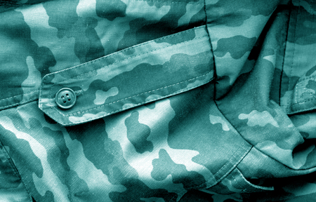 Military uniform pattern with blur effect in cyan tone. Abstract background and texture.