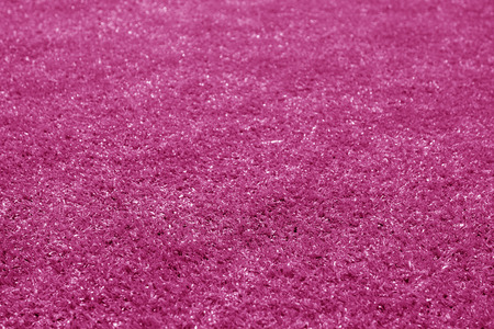 Artificial grass football field loan with blur effect in pink tone. Abstract background and texture for design.
