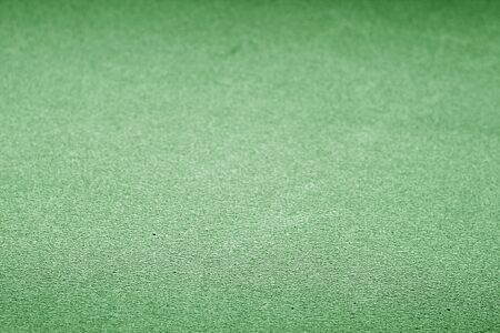 Plastic glittering texture with blur effect in green color. Abstract background and texture for design.