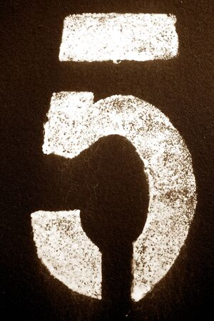 Number 5 in stencil on metal wall in brown tone. Abstract background and texture for design.