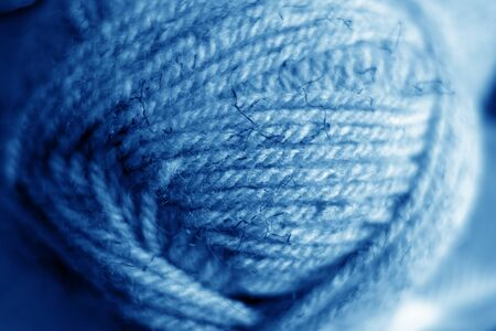 Yarn ball close-up with blur effect in navy blue tone. Abstract background and texture for design. Banco de Imagens
