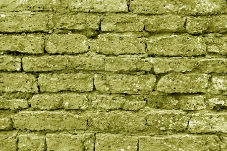 Old grungy brick wall texture in yellow tone. Abstract architectural background and texture for design. Stock Photo