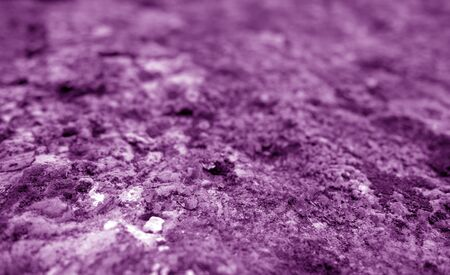 Old stone surface with blur effect in purple tone. Abstract architectural background and texture for design. Stock Photo