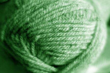 Yarn ball close-up with blur effect in green tone. Abstract background and texture for design. Banco de Imagens