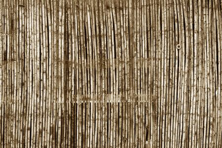 Weathered bamboo fence in brown tone. Abstract background and texture for design.