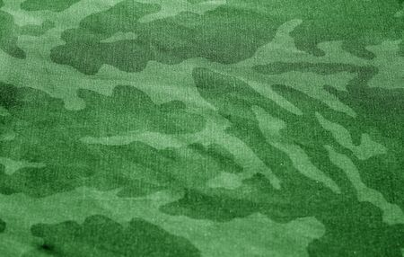 Dirty camouflage cloth with blur effect in green tone. Abstract background and texture for design abd ideas. Imagens