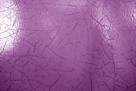 Cracked paint texture in purple color. Abstract architectural background and texture for design.