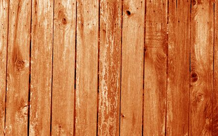 Weathered wooden fence in orange color. Abstract background and texture for design.