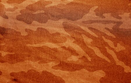 Dirty camouflage cloth with blur effect in orange tone. Abstract background and texture for design abd ideas.