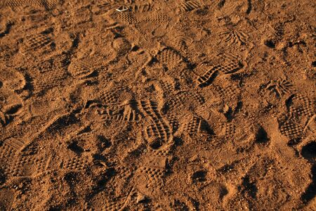 Many footprints in the sand. Abstract background and surface for design.