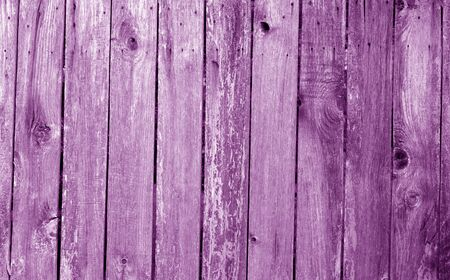 Weathered wooden fence in purple color. Abstract background and texture for design.