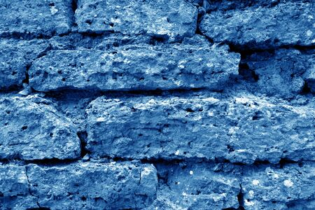 Old grungy brick wall texture in navy blue tone. Abstract architectural background and texture for design.