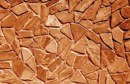 Wall made of old stones in orange tone. Abstract background and texture for design. 写真素材