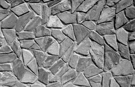 Wall made of old stones in black and white. Abstract background and texture for design.