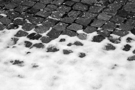 Snow on urban pavement in black and white. Seasonal background for wallpaper or design.