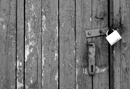 Grungy wooden door with lock in black and white. Abstract architectural background and texture for design.