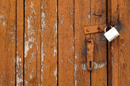 Grungy wooden door with lock. Abstract architectural background and texture for design.