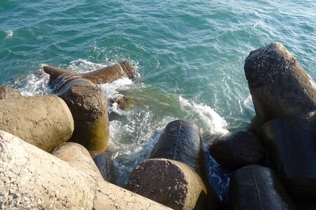 breakwater stones on mole at Black sea. Sea view and vackground