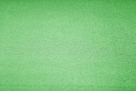 Plastic glittering texture with blur effect in green tone. Abstract architectural background and texture for design.