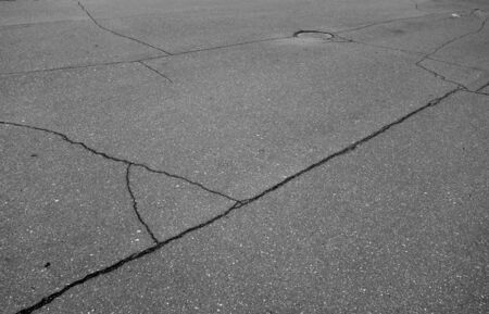 Craked asphalt and red manhole cover in black and white. Industrial background and texture for design.