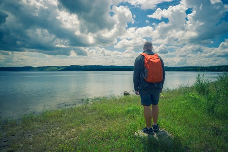 traveler one man with vivid red backpack stand on the rock on a river banks and look at hills at the distance