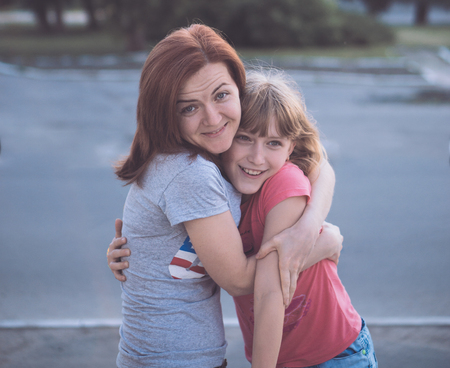 jeune fille adolescente: jolie jeune mère attrayante caucasien amusant avec sa fille adolescente étreint câlins sourire