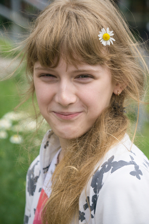 portrait of funny pretty teenage young girl smiling smirk with daisy chamomile flower in her hair blurred background