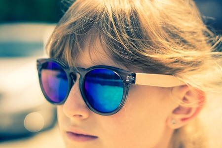 fullface: closeup shot of fullface portrait of teenage young girl in mirrored goggles in soft light. vintage look, selective focus Stock Photo