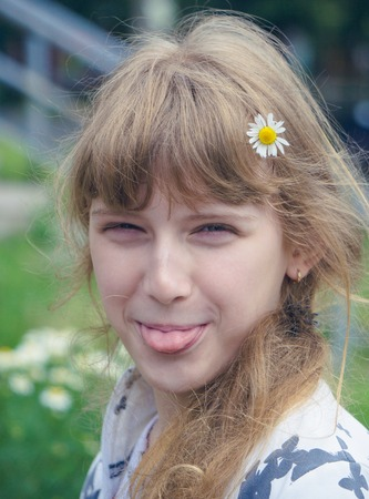 portrait of funny pretty teenage young girl who shows her tongue with daisy chamomile flower in her hair blurred background Stock Photo